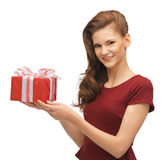 Teenage girl in red dress with gift box Stock Images