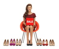 Teenage girl in red dress with shoes and sale sign Royalty Free Stock Photos