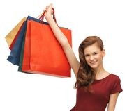 Teenage girl in red dress with shopping bags Royalty Free Stock Photo
