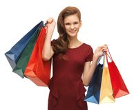 Teenage girl in red dress with shopping bags Royalty Free Stock Photos