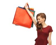 Teenage girl in red dress with shopping bags Stock Photos