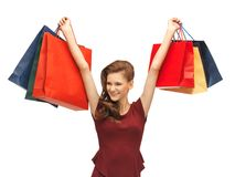 Teenage girl in red dress with shopping bags Royalty Free Stock Photography