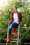 Teenage girl in red gumboots posing on ladder at apple garden Royalty Free Stock Image