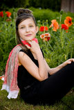 Teenage girl with red scarf and red poppies Stock Photos