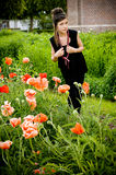 Teenage girl with red scarf and red poppies Stock Image