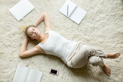 Teenage girl relaxing on the floor of living room. Beautiful young woman holding hands behind head while lying on white carpet on the floor in living room and Royalty Free Stock Images