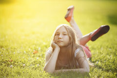 Teenage girl relaxing on grass. With yellow tone, looking to camera Royalty Free Stock Photos