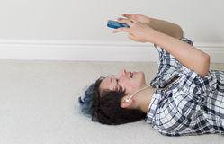 Teenage girl relaxing while on her cell phone and listening to m Stock Photo