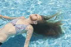 Teenage girl relaxing in the pool Stock Photos