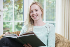 Teenage Girl Relaxing And Reading Book At Home Royalty Free Stock Photos