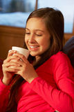 Teenage Girl Relaxing On Sofa With Hot Drink Royalty Free Stock Image