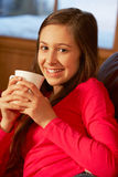 Teenage Girl Relaxing On Sofa With Hot Drink Stock Photos