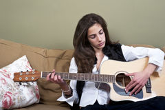Teenage girl playing the guitar Stock Images