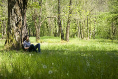 Teenage girl relaxing under a tree Stock Images