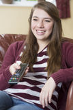 Teenage Girl Relaxing And Watching TV At Home Stock Images