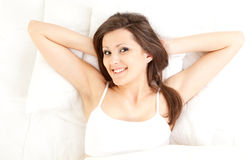 Teenage girl relaxing in white bedding Stock Images