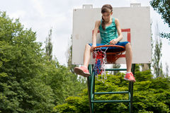 Teenage girl repairing a basketball net Stock Images