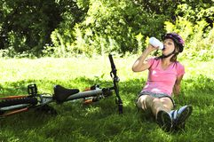 Teenage girl resting in a park with a bicycle Stock Photo