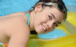 Teenage girl resting in the pool. Young woman resting on a floating cusion in the swimming pool Stock Photography