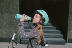 Teenage girl resting in a street with a bicycle drinking water Stock Images