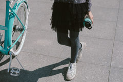 Teenage girl resting in a street with a bicycle drinking water Royalty Free Stock Photos