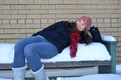Teenage Girl Rests on a Snow Covered Bench Royalty Free Stock Image