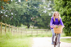 Teenage Girl Riding Bike Along Country Lane. With Flowers In Basket Smiling At Camera stock photos