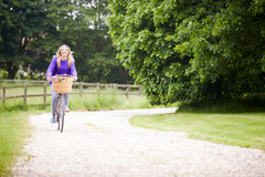 Teenage Girl Riding Bike Along Country Lane. By Herself Smiling To Camera Stock Images