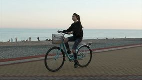Teenage girl is riding a bike along gravel beach in evening near sea, side view stock footage