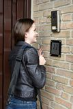 Friendly  teenage girl speks into door-phone Royalty Free Stock Photo
