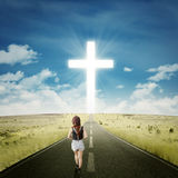 Teenage girl on the road with a cross stock images