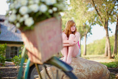 Teenage girl on rock. Teenage girl sitting casually on a rock outdoors Stock Image