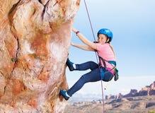 Teenage girl rock climbing high in the mountains. Side view portrait of teenage girl rock climbing with harness high in the mountains royalty free stock image