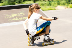 Teenage girl in rollerblades crouching down. Closeup side view of a teenage girl in rollerblades crouching down on the tarmac watching something Royalty Free Stock Images