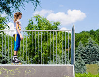 Teenage girl in rollerblades on a ramp Stock Photos