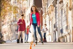Teenage girl rollerblading around the cones stock photography