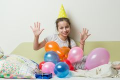 The teenage girl`s birthday is 10 years old. A girl in a festive hat lies with a gift on the bed in a children`s room, girl show stock photos