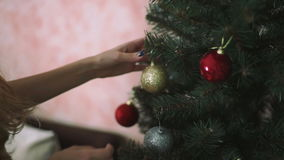 Teenage girl`s hands is decorating a Christmas tree stock footage