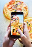 Teenage girl`s hands with smartphone takes picture of homemade pizza royalty free stock photography