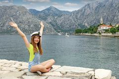 Teenage girl with sailor hat and hands up on summer vacati Stock Photos