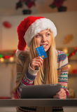 Teenage girl in santa hat with credit card and tablet pc Stock Image