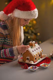 Teenage girl in santa hat decorating christmas cookie house Royalty Free Stock Photo