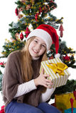 Teenage girl in Santa hat with present under Christmas tree stock photos