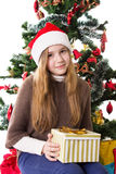 Teenage girl in Santa hat with present under Christmas tree stock photo