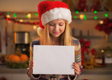 Teenage girl in santa hat showing blank paper sheet in kitchen Stock Photography