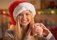 Teenage girl in santa hat showing piggy bank in kitchen Royalty Free Stock Images