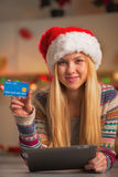 Teenage girl in santa hat with tablet pc showing credit card Stock Images