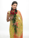 Teenage girl in sari holding red roses Stock Photography