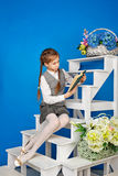 Teenage girl in school uniform reading book. Royalty Free Stock Images
