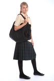 Teenage girl in school uniform and shoulder bag. Teenage girl smiles wearing secondary school student uniform of tartan skirt and beige shirt, with big black Stock Image